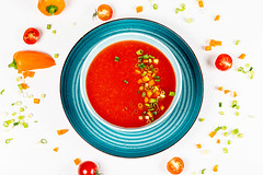 Top view of tomato soup with herbs and bell pepper on a white background
