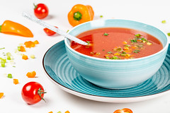 A bowl of fresh tomato soup with herbs and bell pepper