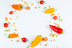 Frame of fresh bell peppers, tomatoes and sliced onions on a white background