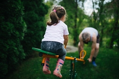 Little girl have fun with her grandfather in the garden.