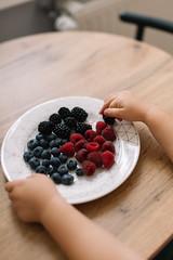 The child takes blueberries, raspberries and blackberries