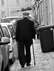 Elderly man walking with a cane on the street