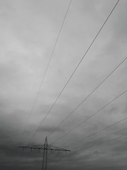 Electric pole power lines outgoing electric wires againts a cloudy sky.