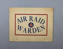 12.4.J Sign Air Raid Warden White with red blue print and Civil Defense Air Warden insignia in center redwhite stripe triangle World War II