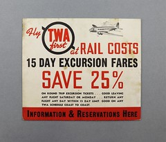 74.8.E Advertisement TWA Fly TWA first at Rail Costs 15 Day Excursion Fares White cardboard sign with red and black print cardboard brop stand in back