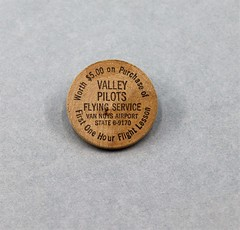 87.8.C  Wooden token Wooden Nickel with image of Native American in headress on one side Valley Pilots Flying Service Van Nuys Airport Worth 5.00 on Purchase of First One Hour Flight Lesson