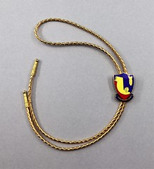 85.93.A Lariat neck wear Braided gold with metal clasp in shield shape with emblem of bomb and Liberandos below Liberandos was a WW II squadron involved in the oil field raids in Romania