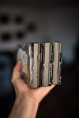 Close-up focused picture of man's hand holding three old hard drives