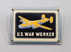 091107.BER.003 Sticker U.S. War Worker Dark blue rectangle with yellow and light blue Consolidated B-24 Liberator in center Mounted in plexi glass frame