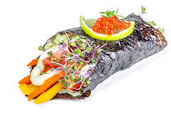 Rice, vegetables, sauce and microgreens wrapped in nori with red caviar and lime