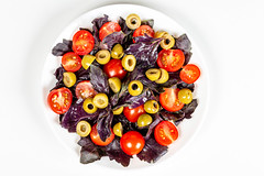 Fresh salad with tomatoes, green olives and red basil, top view
