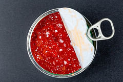 Open iron jar with red caviar on a black background, top view