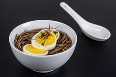 Soup with buckwheat noodles and boiled egg on a black background. Chinese food