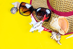 Airplane, multi-colored shells, hat and sunglasses on a yellow background