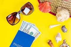 Straw hat, sunglasses, shells with passport and money on yellow background