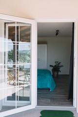Wood door half open with handle in front of bedroom interior background.