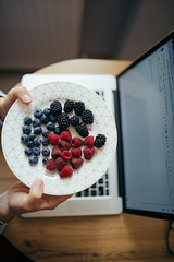 A woman holds a plate with blueberries, cranberries and raspberries from above.