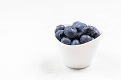 Blueberries in the bowl with copy space above white background