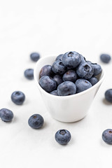 Blueberries in the white bowl above white background