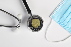 Stethoscope, face mask and silver coin with Donald Trump on white background