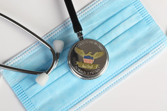 President Donald Trump coin and stethoscope on medical face mask