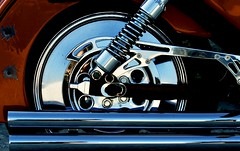The chrome on the rear  road of the red motorbike