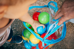Toddler grabbing colorful balls from a transparent bag