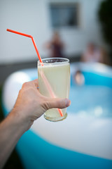 Man in front of a pool holding a glass of lemonade