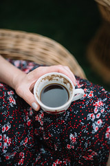 Woman sitting in the yard and holding a cup of coffee