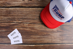 Small papers with vote text and Trump hat on wooden table