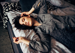 Young adult woman lying on a bed with her eyes closed.