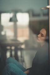 Lonely woman sleeping near window.