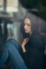 Lonely woman sitting near window.