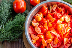 Top view, bowl with sliced fresh red tomatoes