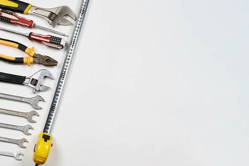Labor day background. Top view of many handy working tools on the white background