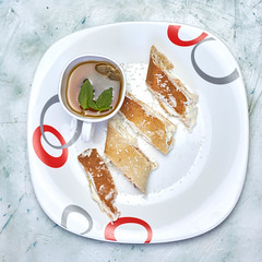 Healthy sweet breakfast. Sliced roulette with soft cottage cheese and a cup of green tea