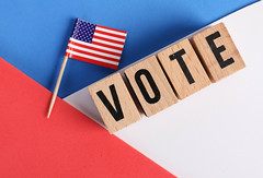 Vote word written on wooden blocks and American flag