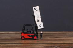 Businessman standing under wooden blocks with risk text