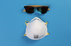Protective mask and sunglasses on blue background
