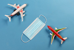 Two toy airplanes with protective mask on blue background