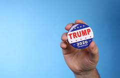 Hand holding Trump 2020 badge on blue background