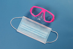 Medical face mask and diving mask on blue background