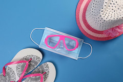 Medical face mask and diving mask with flipflops and sun hat on blue background