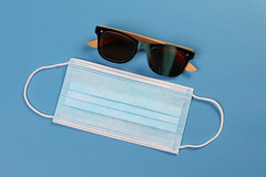 Medical face mask with sunglasses on blue background