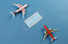 Two toy airplanes with medical face mask on blue background