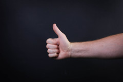 Male hand is showing a thumbs up gesture sign on black background