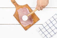 Cook beats Pork Raw Meat with wooden hammer