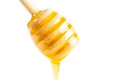 Natural bee honey flows down a wooden honey dipper
