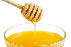 Honey bowl with dipper and flowing honey