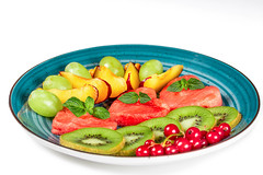 Plate with sliced ripe fresh fruit and berries